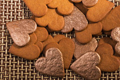 Gingerbread hearts heaped out with gold hearts. On cane background Stock Photography
