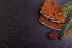 Gingerbread honey-cake with raisins decorated with icing, spruce branches, cinnamon sticks, star anise Stock Photo