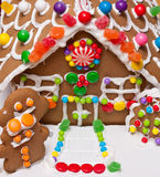 Gingerbread house. Closeup of gingerbread house with windows, roof, front door and gingerbread men royalty free stock photos