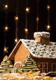 Gingerbread house. Beautiful gingerbread house with lights on dark background stock image