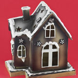 Gingerbread House. A festively decorated gingerbread house isolated against a red background Royalty Free Stock Photo