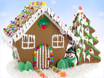 Gingerbread house. And christmas tree on the snowflake background stock image