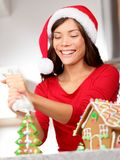 Gingerbread house. Young santa hat woman in Christmas preparations putting icing on . Mixed race Asian / Caucasian woman model wearing santa hat stock photo