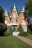 Gingerbread House. An ornate, nineteenth-century North American red brick house in late summer Stock Images