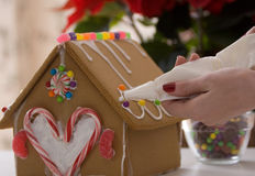 Gingerbread House being Decorated Stock Images