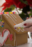 Gingerbread House being Decorated Stock Photos