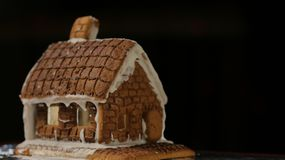 Gingerbread House Black Background. Gingerbread house with dark background Christmas garland Happy New Year stock photo