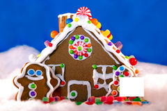 Gingerbread house with blank sign. Holiday Gingerbread house with blank sign in front yard stock photo