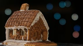 Gingerbread House Blue Lights. Gingerbread house with blue lights bokeh circles blur Christmas garland Happy New Year royalty free stock image