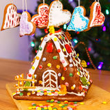 Gingerbread house with Christmas tree and lights on background. Stock Photos