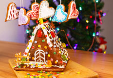 Gingerbread house with Christmas tree and lights on background. Stock Image