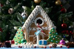 Gingerbread house with Christmas trees. Xmas candy and gift boxes under the tree. Traditional homemade christmas cookies with colorful candy decoration stock image