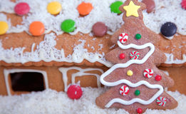 Gingerbread house covered in snow. Spotlit gingerbread house with candy and snow Stock Image