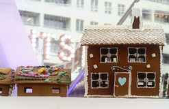 Gingerbread house decorated for Christmas. Decorated gingerbread houses with white frosting and ornament details and a heart in blue and candy covered roof royalty free stock photography