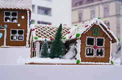 Gingerbread house decorated for Christmas. A decorated gingerbread house with white frosting and ornament details in green and red with a little snow covered royalty free stock image