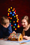 Gingerbread house decoration. Family decorating gingerbread house on Christmas eve royalty free stock photography