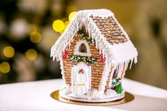 Gingerbread house in front of defocused lights of Christmas decorated fir tree. Holiday sweets. New Year and Christmas theme. royalty free stock image