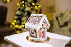 Gingerbread house in front of defocused lights of Christmas decorated fir tree. Holiday sweets. New Year and Christmas theme. Festive mood. Christmas card royalty free stock images