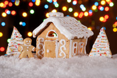Gingerbread house with gingerbread man and christmas trees stock images