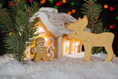 Gingerbread house with gingerbread man, elk and christmas trees. Royalty Free Stock Photography