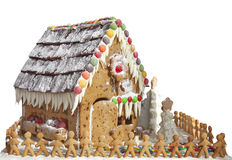 Gingerbread House with Gingerbread Men. A colorful gingerbread house isolated on a white background with a line of small gingerbread men holding hands royalty free stock images