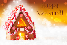 Gingerbread House, Golden Background, Text Happy Weekend. Gingerbread House In Snowy Scenery As Christmas Decoration. Candlelight For Romantic Atmosphere. Golden Royalty Free Stock Photos