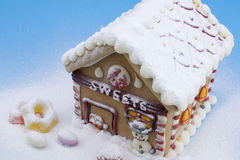 Gingerbread house and other sweets. On blue background Stock Photography