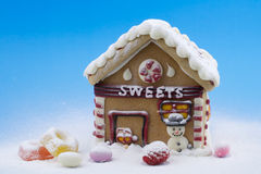 Gingerbread house and other sweets. On blue background Royalty Free Stock Photos