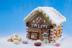 Gingerbread house and other sweets. On blue background Royalty Free Stock Images