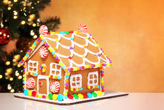 Gingerbread House over Decorated Christmas Tree Royalty Free Stock Image