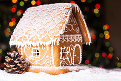 Gingerbread house. Over defocused lights of Chrismtas decorated fir tree stock image