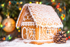 Gingerbread house. Over defocused lights of Chrismtas decorated fir tree stock images