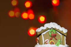 Gingerbread house and over defocused lights. Christmas background royalty free stock image