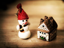 Gingerbread house over  and lovely handmade snowman Royalty Free Stock Photography