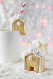 Gingerbread house put on a white cup on the background of bokeh and snow Stock Image