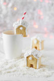 Gingerbread house put on a white cup on the background of bokeh and snow Stock Photos