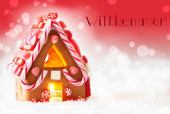 Gingerbread House, Red Background, Text Willkommen Means Welcome. Gingerbread House In Snowy Scenery As Christmas Decoration. Candlelight For Romantic Atmosphere stock photography