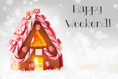 Gingerbread House, Silver Background, Text Happy Weekend. Gingerbread House In Snowy Scenery As Christmas Decoration. Candlelight For Romantic Atmosphere. Silver Stock Image