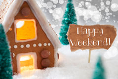 Gingerbread House, Silver Background, Text Happy Weekend. Gingerbread House In Snowy Scenery As Christmas Decoration. Christmas Trees And Candlelight For Stock Image