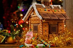 Gingerbread house with sweets and a Christmas toy pig on the background of the Christmas tree. stock photos