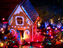 Gingerbread houses with christmas lights string on wooden table. Royalty Free Stock Photography