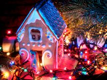 Gingerbread houses with christmas lights string on wooden table. Stock Photo