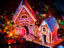 Gingerbread houses country with christmas lights string on wooden table. Stock Photo