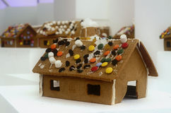 Gingerbread houses decorated for Christmas. Decorated gingerbread houses with white frosting and ornament details and a candy covered roof on a white background stock images