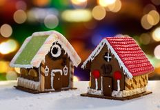 Gingerbread houses over christmas lights. Cooking, holidays and bakery concept - gingerbread houses over christmas lights background royalty free stock photo