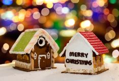 Gingerbread houses over christmas lights. Cooking, holidays and bakery concept - gingerbread houses over christmas lights background stock images