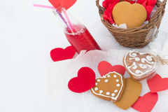 Gingerbread and lemonade with paper hearts on the snow. Gingerbread and cranberry lemonade with paper hearts on the snow Stock Photography