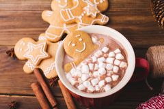 Gingerbread man bathes in a cup of chocolate or cocoa with marshmallow. Gingerbread Man in red cup Royalty Free Stock Photos