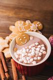 Gingerbread man bathes in a cup of chocolate or cocoa with marshmallow. Gingerbread Man in red cup Stock Images