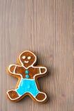 Gingerbread man on black velvet on wooden table. In christmas stock images